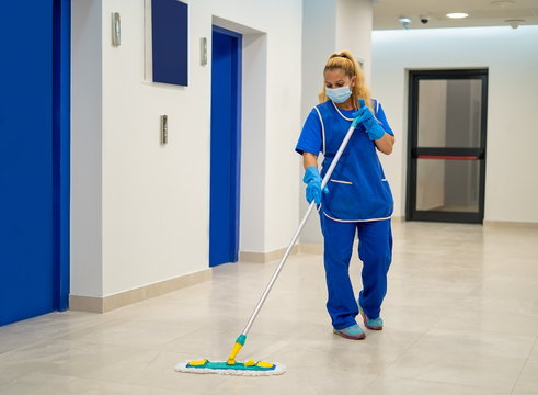 A cleaning lady with a mask on her face cleans the hallway