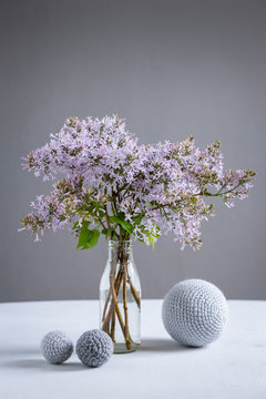 Wool spheres and bottle with blooming lilacs