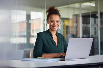 Portrait of smiling businesswoman working on laptop at desk