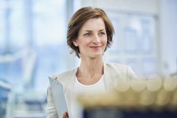 Thoughtful female manager holding clipboard in factory