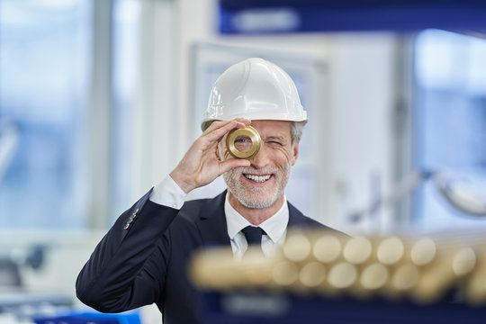 Happy male manager in white hardhat looking through brass object in factory