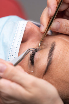 Hands of beautician using tweezers on customer for eyelash extension at beauty spa