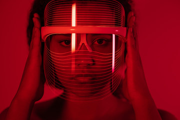 Close-up of woman wearing red light therapy mask against wall at home