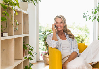 Portrait of happy mature woman on the phone relaxing in armchair at home