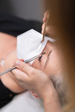 Close-up of female customer getting eyelash treatment from beautician at spa