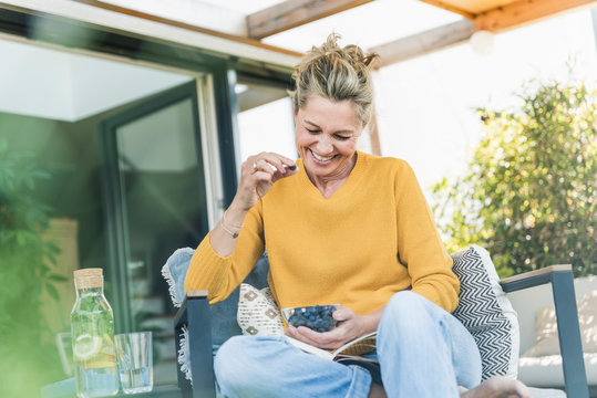 Portrait of laughing mature woman sitting on terrace eating blueberries