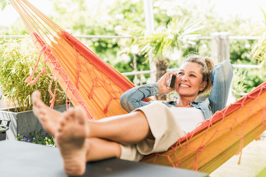 Portrait of happy mature woman on the phone relaxing in hammock on terrace