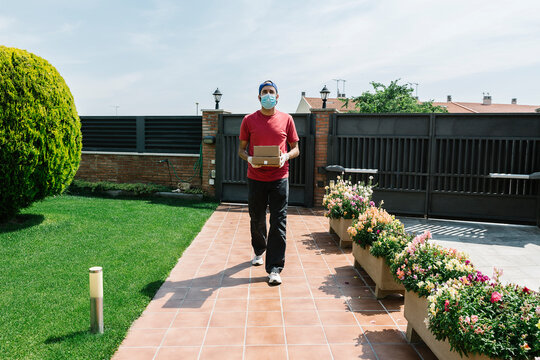 Male delivery person with package on footpath against gate