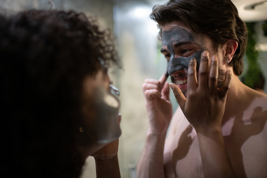 Blurred African American female helping cheerful boyfriend to smear clay on face during spa procedure at home