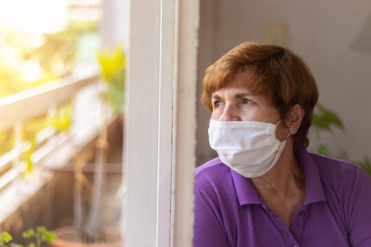 Elderly watches through the window of her house, while being confined by the coronavirus quarantine