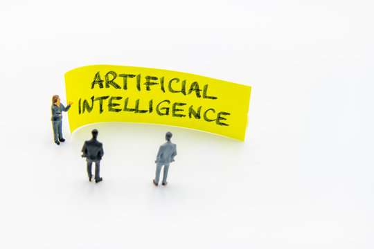 Presentation meeting with miniature figurines posed as business people standing in front of post-it note with Artificial Intelligence handwritten message in background, copy space on the right