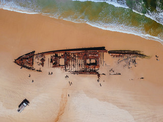 Drone shot of SS Maheno ship wreck directly overhead on Fraser Island in Australia. Sea and waves with sand and people sightseeing from the top view aerial
