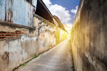 Ancient brick wall in narrow alley in Thailand with vintage warm light, outdoor day light