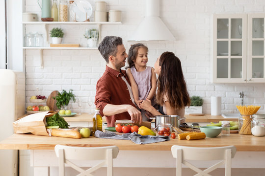 Happy parents with daughter cooking on kitchen