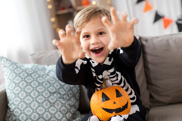 halloween, holiday and childhood concept - smiling little boy in party costume of skeleton with jack-o-lantern pumpkin sitting on sofa and having fun at home
