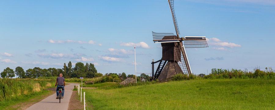 Tourist passing Windmill the Monnikenburenmolen or Nijhuizumermolen a drainage mill in Nijhuizum, Friesland, Netherlands.