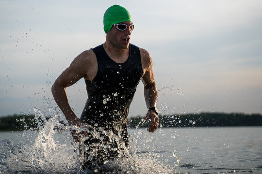 The triathlete runs out of the water. Swimming training.