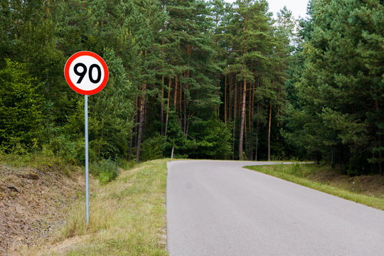 Speed limit sign with trees behind. Maximum ninety kilometers per hour. Safety on road in forest background. White round sign red border line.