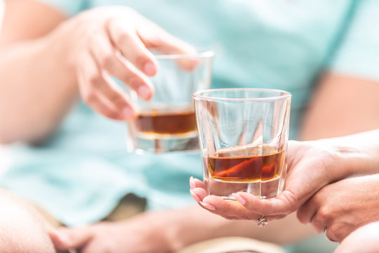 Man and woman hands toasting with glasses of whiskey brandy or rum indoors - closeup
