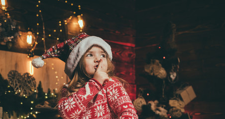 Happy Christmas little girl is having a secret. Beautiful little girl wearing Santa hat. Christmas...