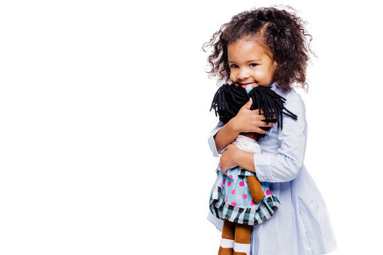 Portrait of a cute little african american girl hugging doll, isolated on white background.