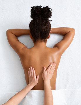 Therapist massaging african woman back, top view
