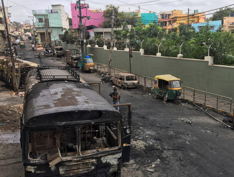 Television news camera operator films burnt police bus and other private vehicles after violence erupted between police and protesters over a reported derogatory Facebook post about Islam's Prophet Mohammad in Bengaluru