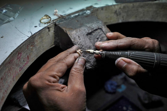 An employee fills a ring at a diamond jewellery manufacturing factory in Mumbai