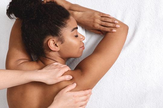 Closeup of black young woman having healing body massage