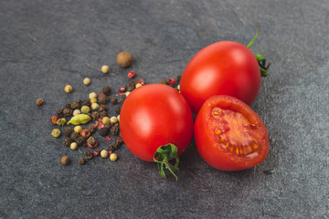 Cherry tomatoes on a black background with various spices. Seasoning and tomato