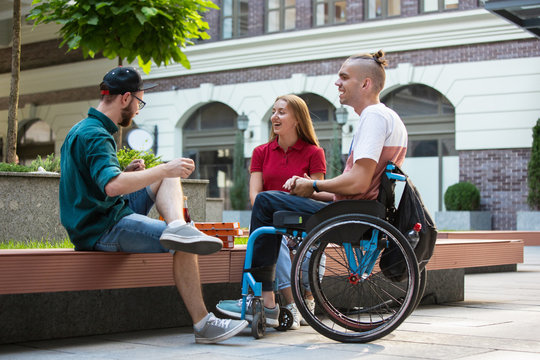 Group of friends taking a stroll on city's street in summer day. Disabled, handicapped man with his friends having fun. Inclusion and diversity concept, normal lifestyle of special groups of society.