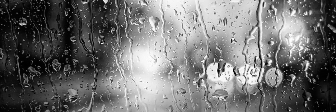 Panoramic image. Blurred car lights in black and white. Raindrops on the front window
