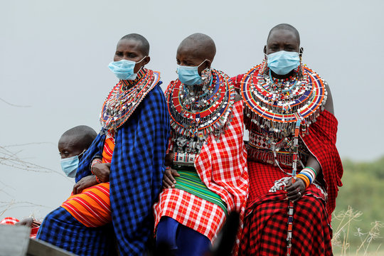 Masai women dressed in traditional clothes wear surgical masks as they wait for a ceremony marking World Elephant Day in the Amboseli National Park