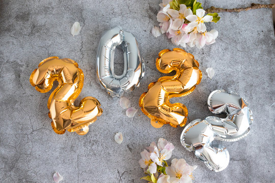 gold and silver 2022 balloons numbers on a concrete background
