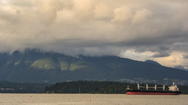 Cargo ferry in the coast of Vancouver surrounded by Mountains