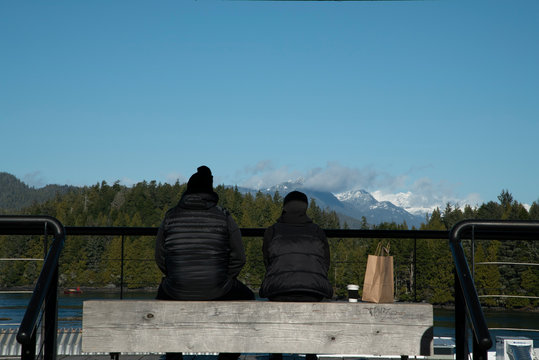 A couple sitting on a bench and observing the view in Vancouver Island, Tofino