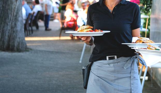 Serviererin bedient Gäste in einem Restaurant, Gastronomie