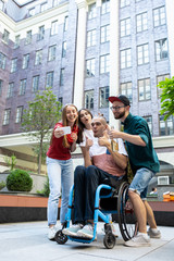 Taking selfie. Group of friends taking a stroll on city's street in summer day. Handicapped man with his friends having fun. Inclusion and diversity concept, normal lifestyle of special groups of