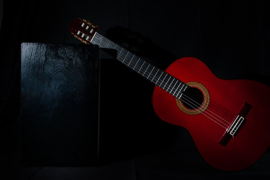 spanish classical red guitar with flamenco cajon on a black background