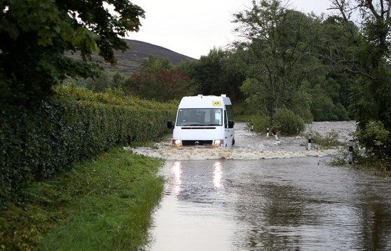 A school minibus drives through a flooded road, in Kirriemuir, Scotland
