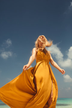 Young woman in yellow dress dancing on beach