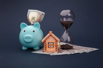 Blue piggy bank with wooden model of house, hourglass and money banknotes on blue background. Savings money for buy house.