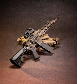 AR 15 style rifle displayed on top of gear, shot in studio.