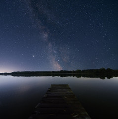 night sky over lake with litle pier