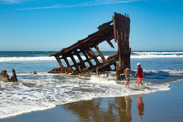 Hammond, Oregon - 8/21/2013:  Children playing in the surf at the remains of the wreck of the sailing ship, the Peter Iredale,  on the beach at Fort Stephens State park in Oregon.