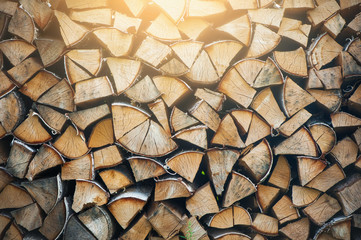 A neatly folded log made of chopped wood. Preparation of firewood for the winter. Rural life. Melting fire. background for text. A sunbeam shines from above