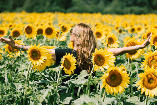 woman with open arms in a sunflowers field.