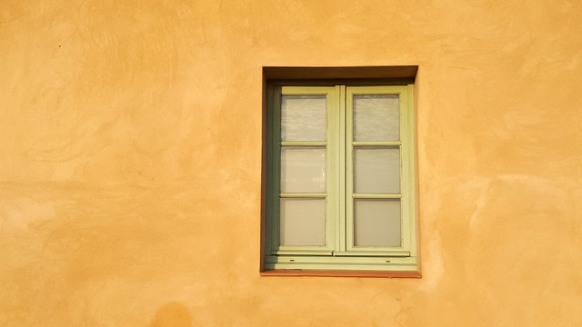 Sonnenbeschienene Hauswand, gelber Putz, Sprossenfenster