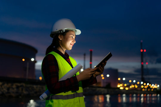 Asian woman petrochemical engineer working at night with digital tablet Inside oil and gas refinery plant industry factory at night for inspector safety quality control..