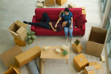 couple take relax after unpacking cardboard from house moving